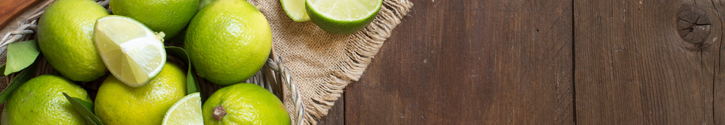A basket of limes on a wooden background.